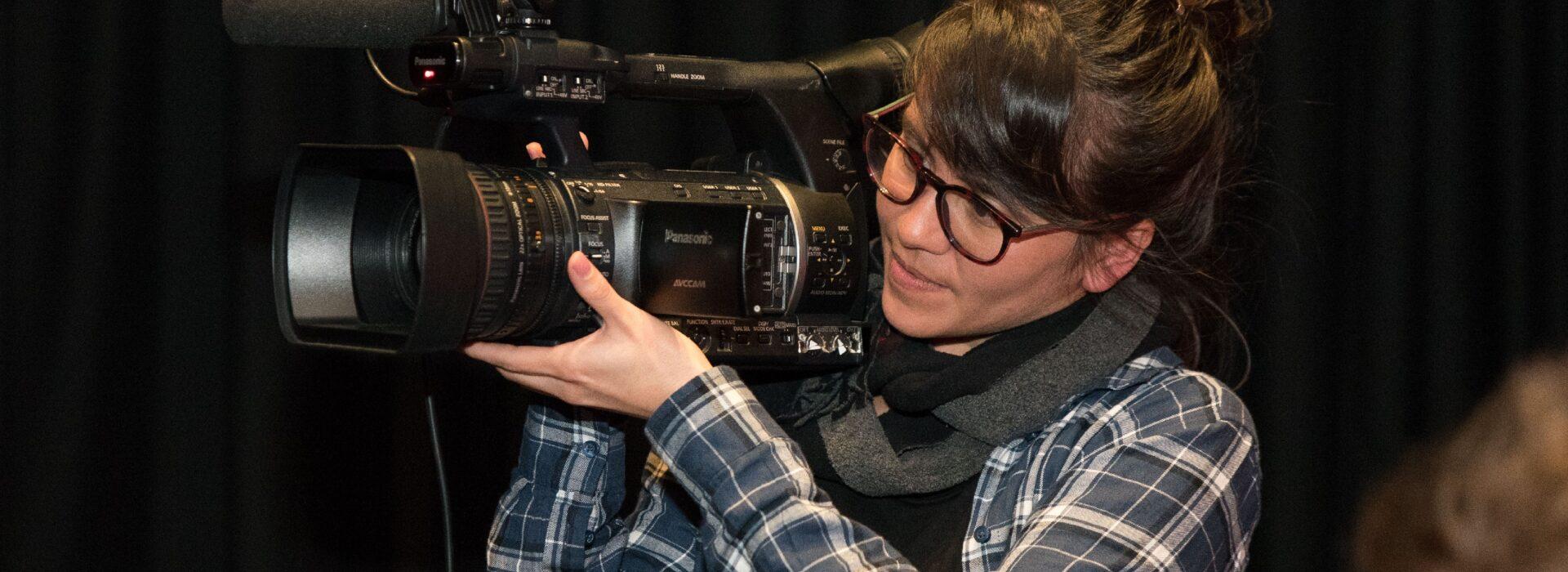 Foto: Kamerafrau mit Kamera auf Schulter