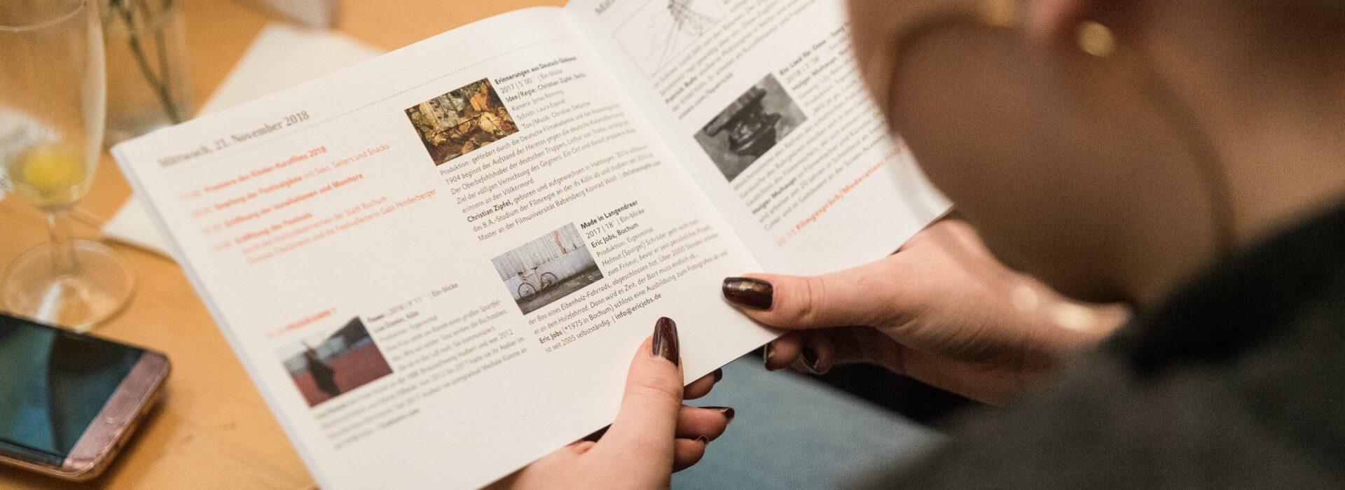 Foto: blicke Programmheft in der Hand einer Leserin
